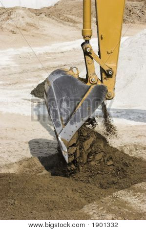 Excavator Dumping Its Load Of Dirt.