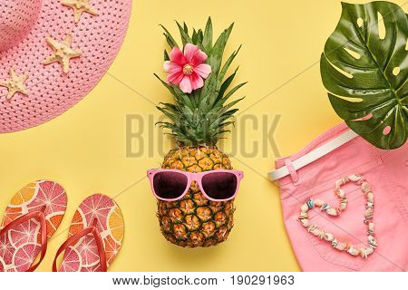 poster of Fashion Pineapple. Bright Summer Color. Clothes Accessories set. Creative Art concept. Fashion woman Swimsuit Bikini, Tropical pineapple. Stylish girl. Minimal. Summer background on yellow. Top View