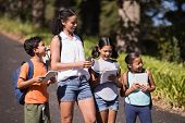 Happy students and teacher with digital tablets standing on street during summer field trip poster