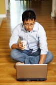 image of self-employment  - An asian businessman sitting on the floor and working on his laptop at home - JPG