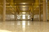 stock photo of school building  - An empty high school corridor with a bright light at the end of the hallway - JPG