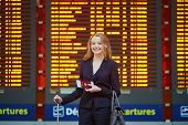 Woman With Hand Luggage In International Airport Terminal, Looking At Information Board poster