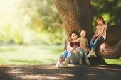 Mother and daughters sitting under the tree on summer lawn. Happy family playing outdoors. Pretty yo poster