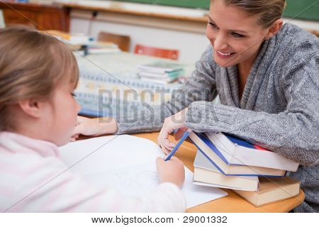 Schoolgirl writing with her smiling teacher in a classroom