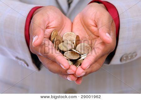 Businessman hand with Indian rupee coins.