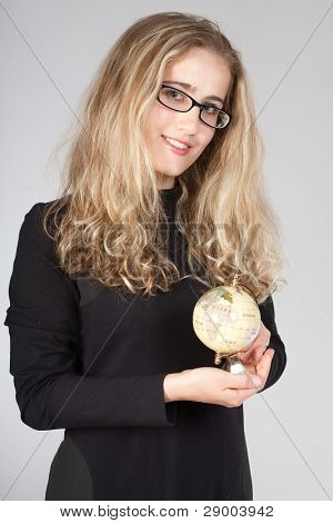 The young emotional girl in points and with the globe in hands