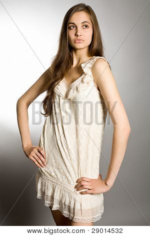 Portrait of the young long-haired girl in an elegant dress on a gray background