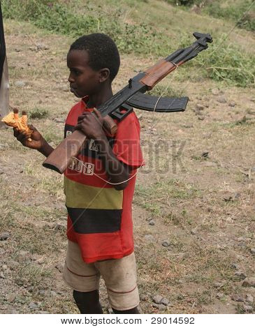 A yougn Ethiopian boy carrying a hand carved rifle as a toy