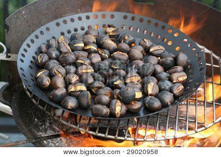 Asar castañas en el fuego de la barbacoa