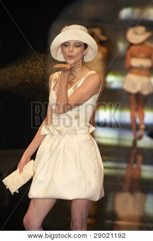 Fashion model in white dress and hat blowing off the gold dust on fashion show