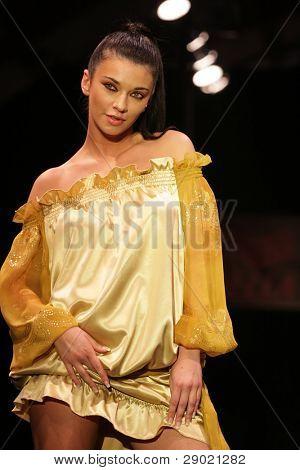 Fashion model posing in golden silk dress