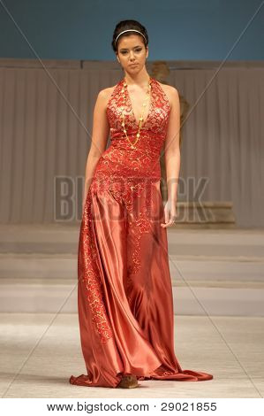 Model in red dress coming down the runway