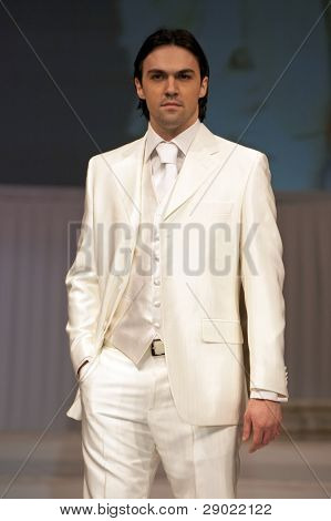Young man in classic, elegant white suit holding one hand in pocket
