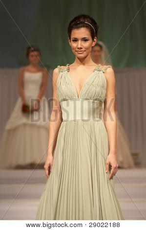 Fashion model in silk greenish dress
