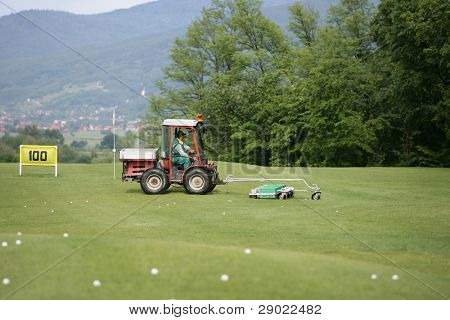 Golf course and a vehicle collecting golf balls