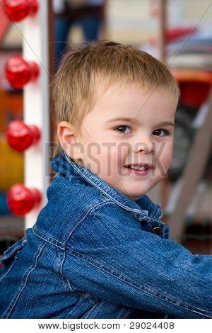 Portrait of a cute toddler boy in a luna park