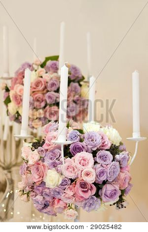 Detail of a colorful rose bouquets with candles