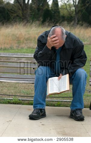 Sad Man Holding Bible