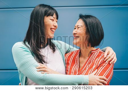 poster of Asian Mother And Daughter Embracing Outdoor - Happy Chinese Family Enjoying Time Outside - Parenthoo
