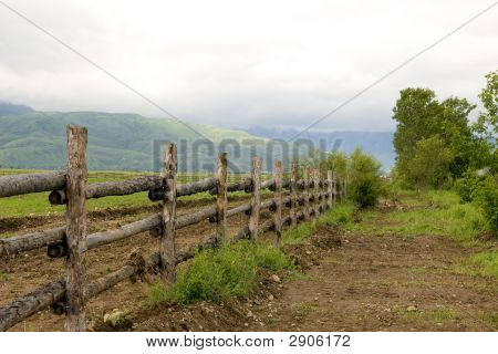 Green Pasture And Wood Fence In Summer Morning At Mountains Tien Shan, Fog After Rain