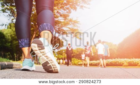 poster of Young Fitness Woman Legs Walking With Group Of People Exercise Walking In The City Public Park In Mo