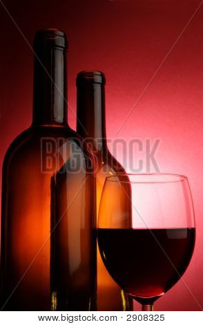 Glass Of Red Wine And Two Bottles