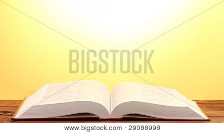 Open book on wooden table on yellow background