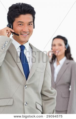Smiling customer support employee with colleague behind him against a white background