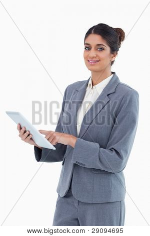 Smiling saleswoman using tablet computer against a white background
