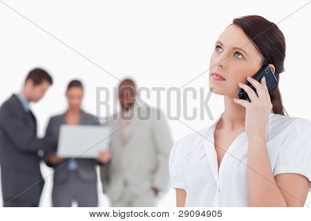 Businesswoman listening to caller with colleagues behind her against a white background