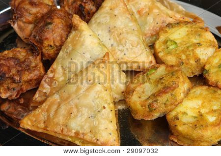 Indian samosa, onion bhaji and pakora on serving tray