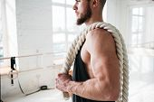 Strong Male Athlete Holding On Shoulder Rope After Intense Workout. Portrait Of Fitness Man With Bat poster