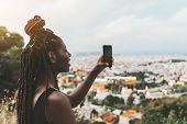 Side View Of A Young Charming Smiling African Female With Braids Is Photographing Amazing Cityscape  poster
