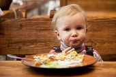 pic of ruddy-faced  - Blond little girl in front of a big plate of food - JPG