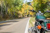 A Green Motorcycle Alongside A Curving Open Road In The Fall.  Selective Focus On Motorcycle With Co poster