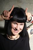 pic of bitchy  - a woman with black hair and piercing shows horns - JPG