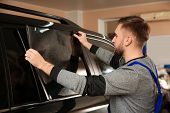 Worker Tinting Car Window With Foil In Shop poster