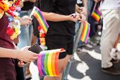 Hands Of A Girl Holding A Smartphone Telephone With A Camera And A Rainbow Gay Flag During A Gay Pri poster