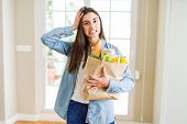 Beautiful young woman holding paper bag full of healthy groceries stressed with hand on head, shocke poster