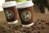stock photo of latte coffee  - Two paper cup of coffee to go on a table with coffee beans - JPG