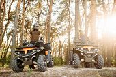 Two atv riders in helmets raise their hands up poster