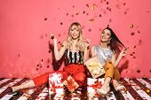 Portrait of two cheeky women 20s in stylish outfit celebrating and sitting on floor with bunch of pr poster