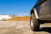Off Road 4X4 Car In The Snowy Mountains On A Sunny Day. Off-road Traveling, All Terrain Vehicle In N poster