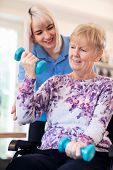 Female Physiotherapist Helping Senior Woman In Wheelchair To Lift Hand Weights poster