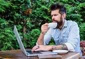 Balancing Between Work And Pleasure. Hipster Drinking Tea And Using Computer Work Station Outdoor. B poster