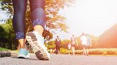 Young Fitness Woman Legs Walking With Group Of People Exercise Walking In The City Public Park In Mo poster