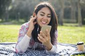 Cheerful Beautiful Girl Having Video Chat Outdoors. Young Woman In Earphones Resting On Plaid In Par poster