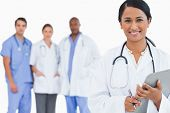 image of medical staff  - Smiling doctor with clipboard and members of staff behind her against a white background - JPG