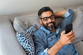 Happy smiling latin man using smartphone device while sitting on sofa at home. Mature indian man lyi poster