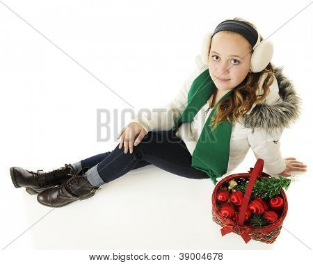 Overhead view of a pretty preteen sitting in her winter-wear by a Christmas basket filled with ornaments.  On a white background.